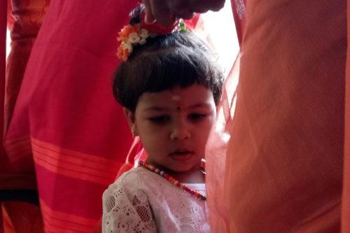 Bambino tra i tessuti indiani rossi