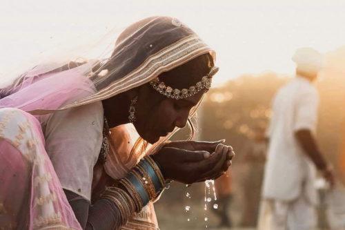 ragazza che beve dal fiume indiano